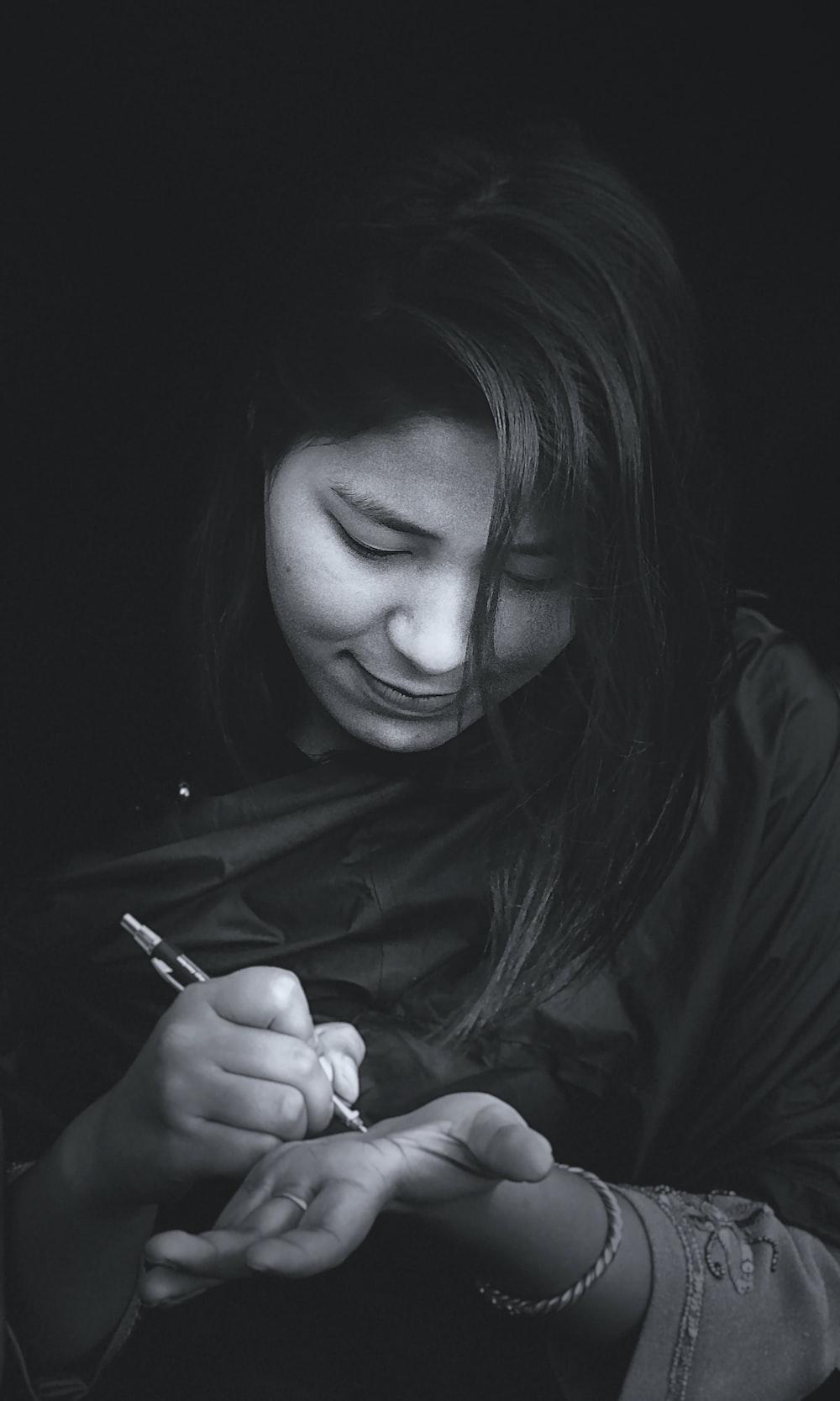 woman in black jacket holding pen