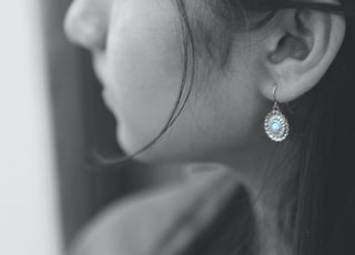 grayscale photo of woman wearing silver diamond stud earring
