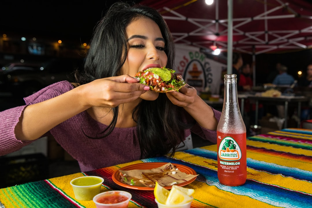 A woman eats a tostada at a street taco stand in Los Angeles at night.