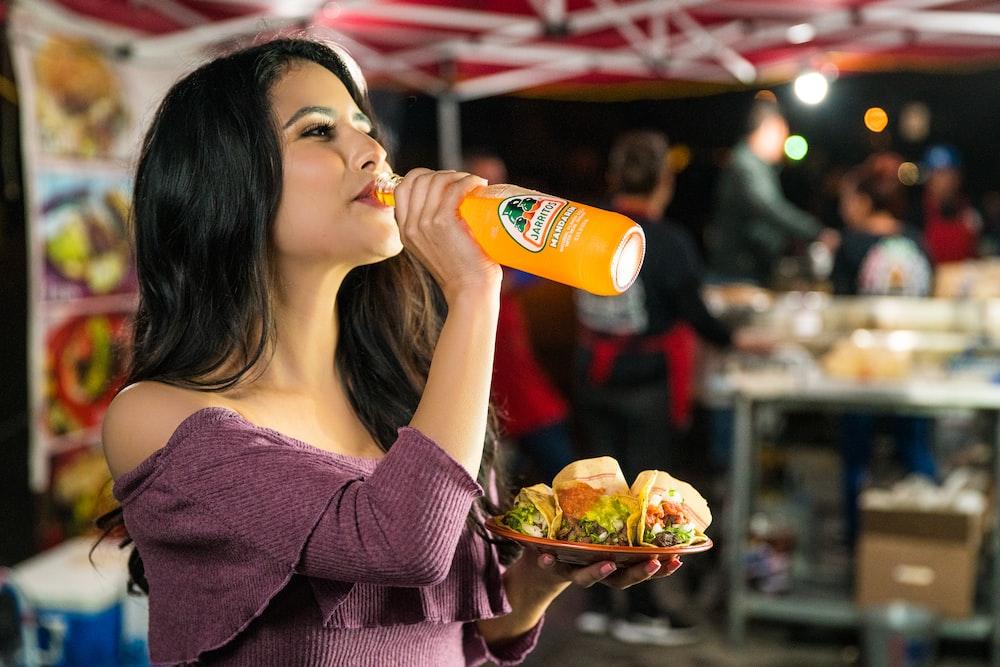 woman in purple long sleeve shirt drinking orange juice