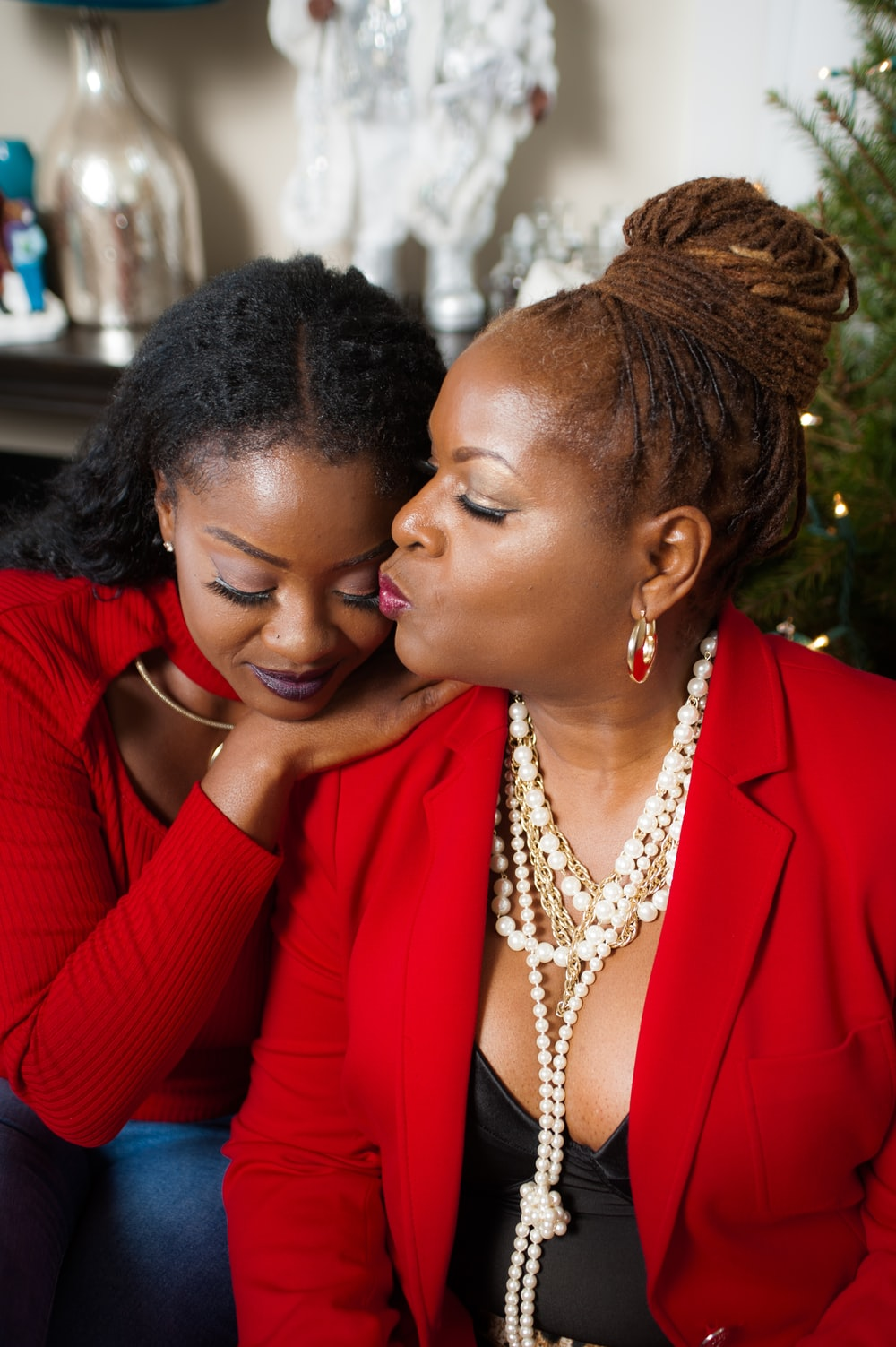 woman in red blazer kissing woman in gold necklace