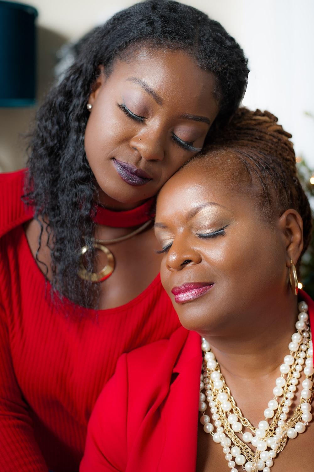 woman in red shirt beside woman in gold earrings