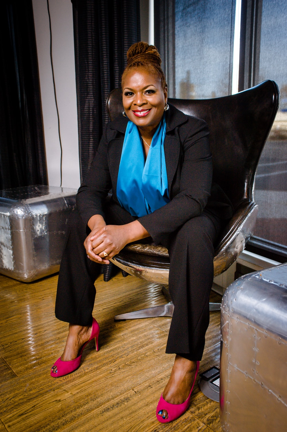 woman in black trouser suit sitting on black leather chair smiling