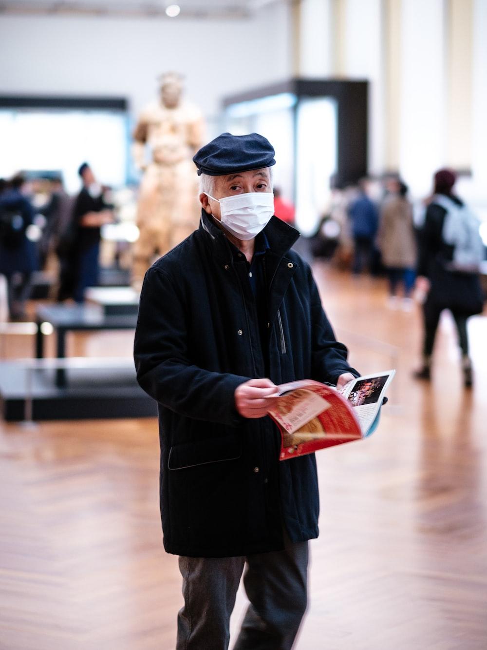 man in black coat holding book
