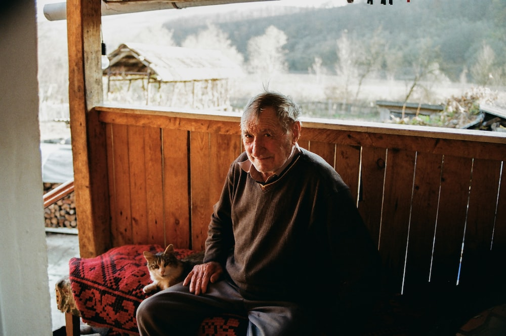 man in brown sweater sitting on chair