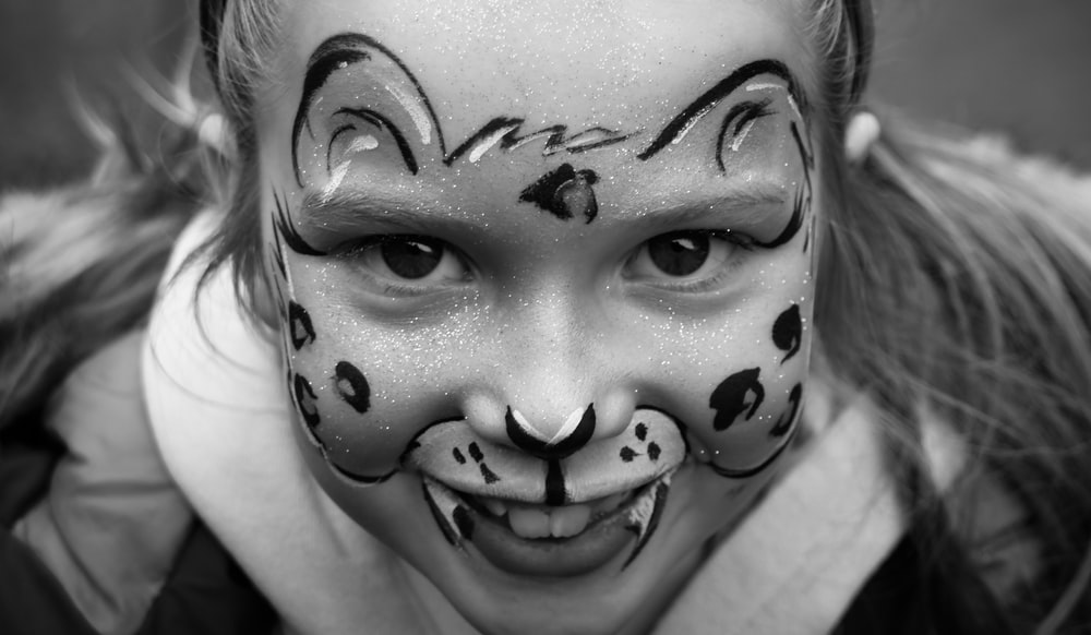 grayscale photo of girl with face paint