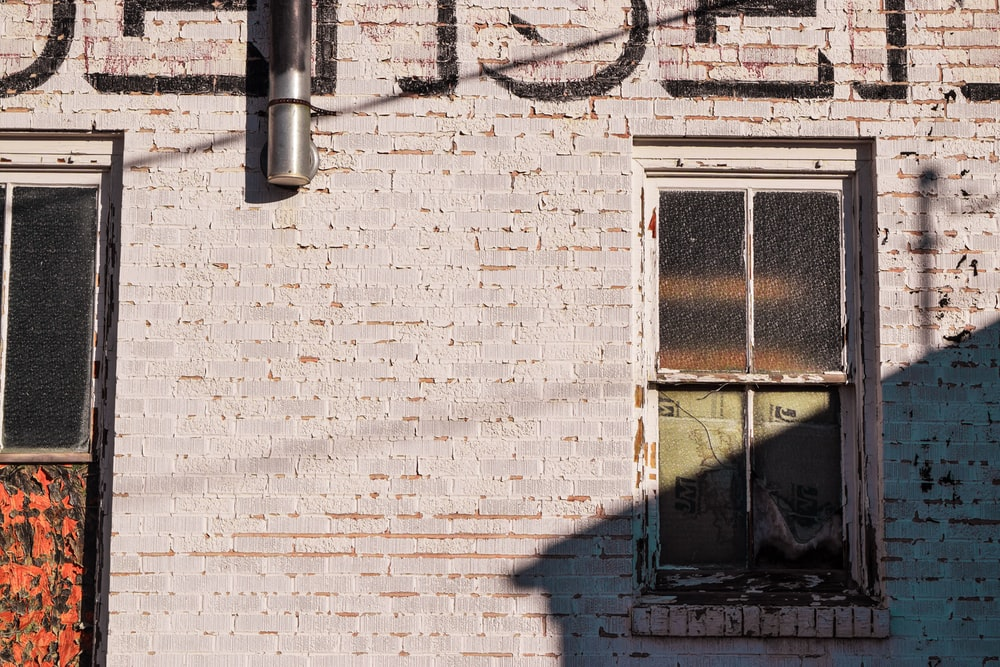 black metal framed window on brick wall