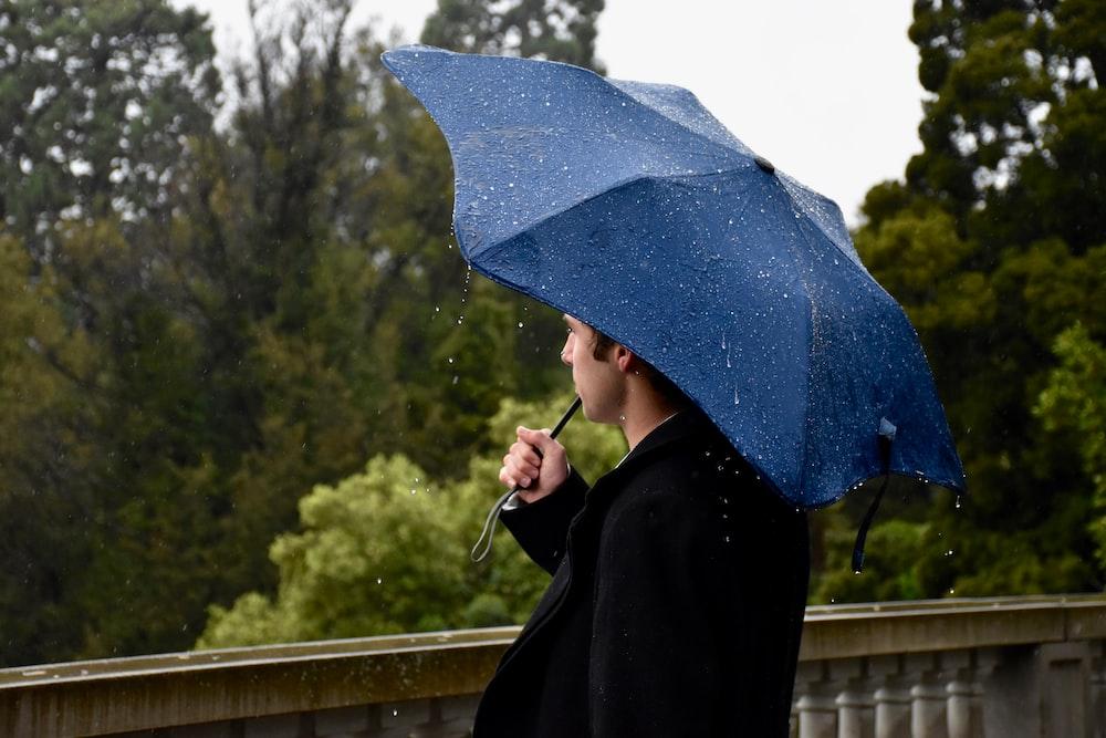 person in black coat holding blue umbrella