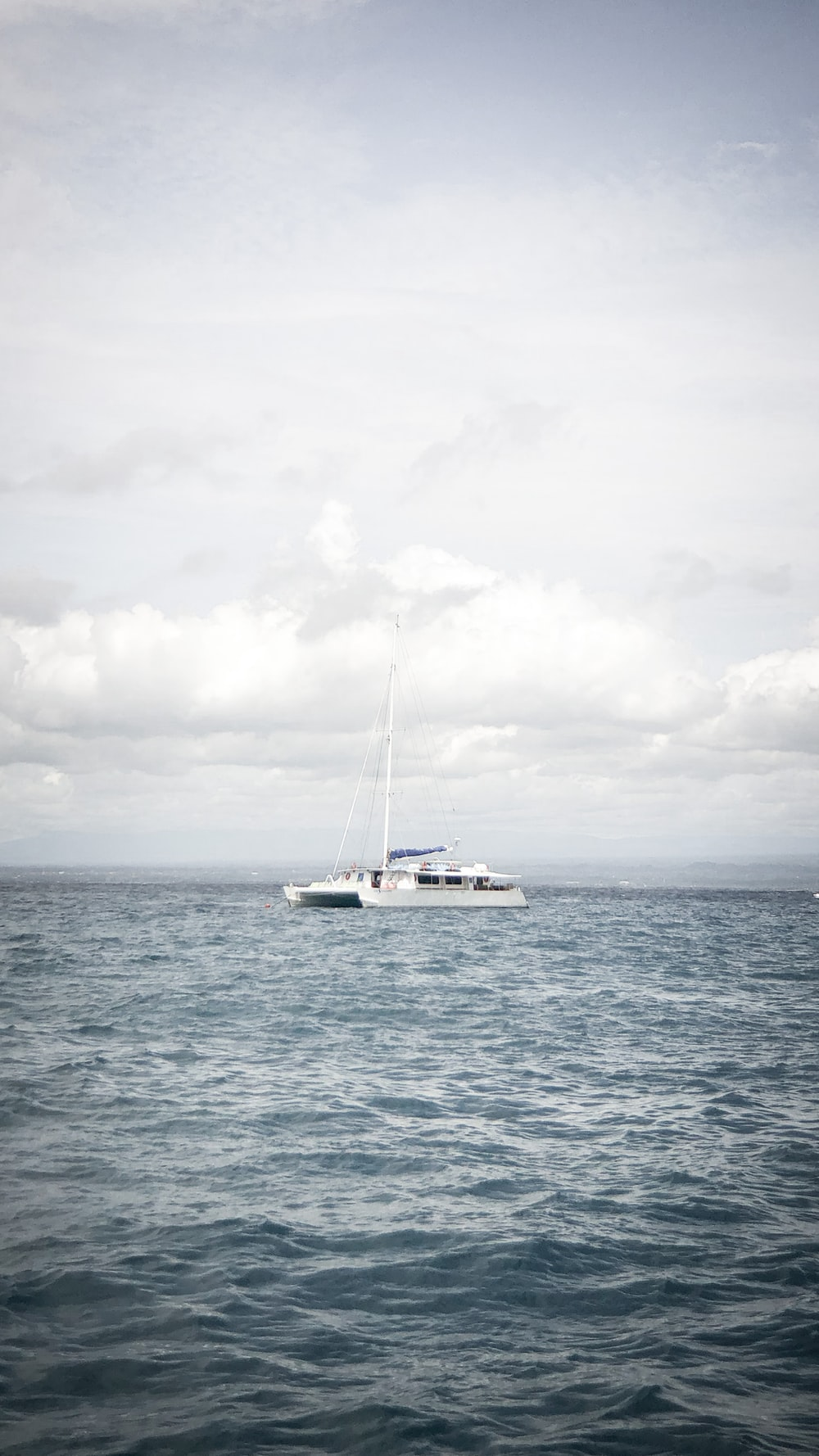 white boat on sea under white clouds during daytime