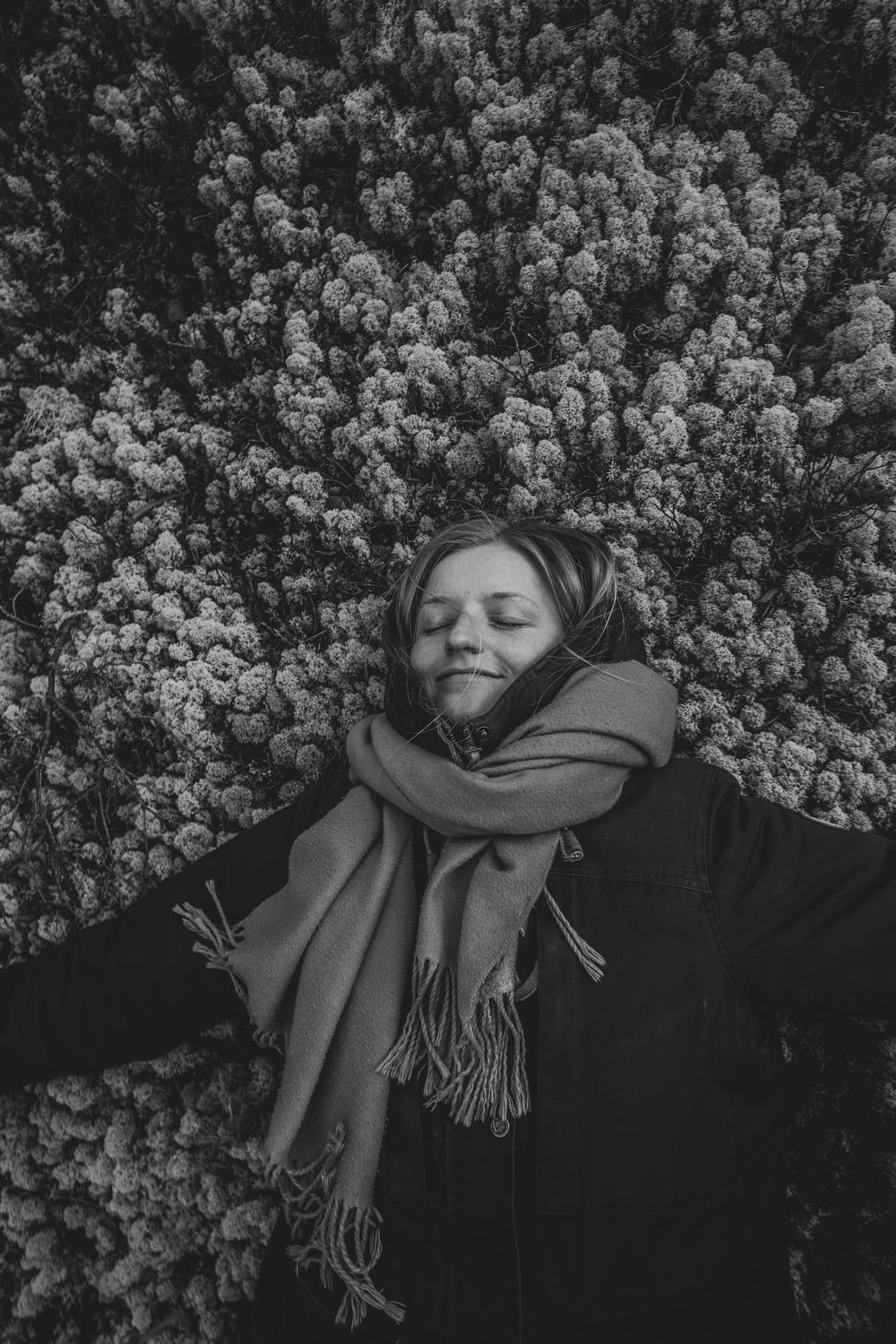 grayscale photo of woman in scarf and jacket