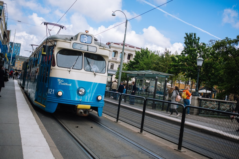 people walking on street near blue and white tram during daytime