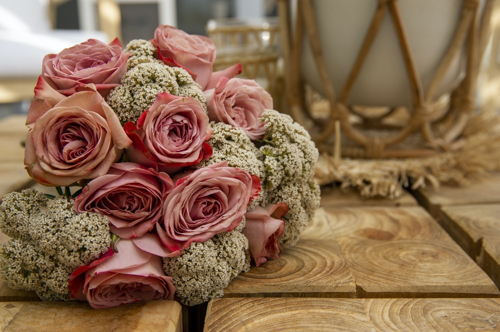 pink roses bouquet on brown wooden table