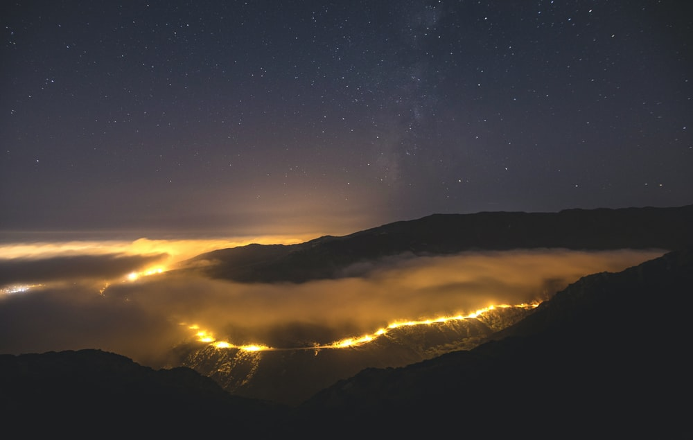 silhouette of mountains under starry night