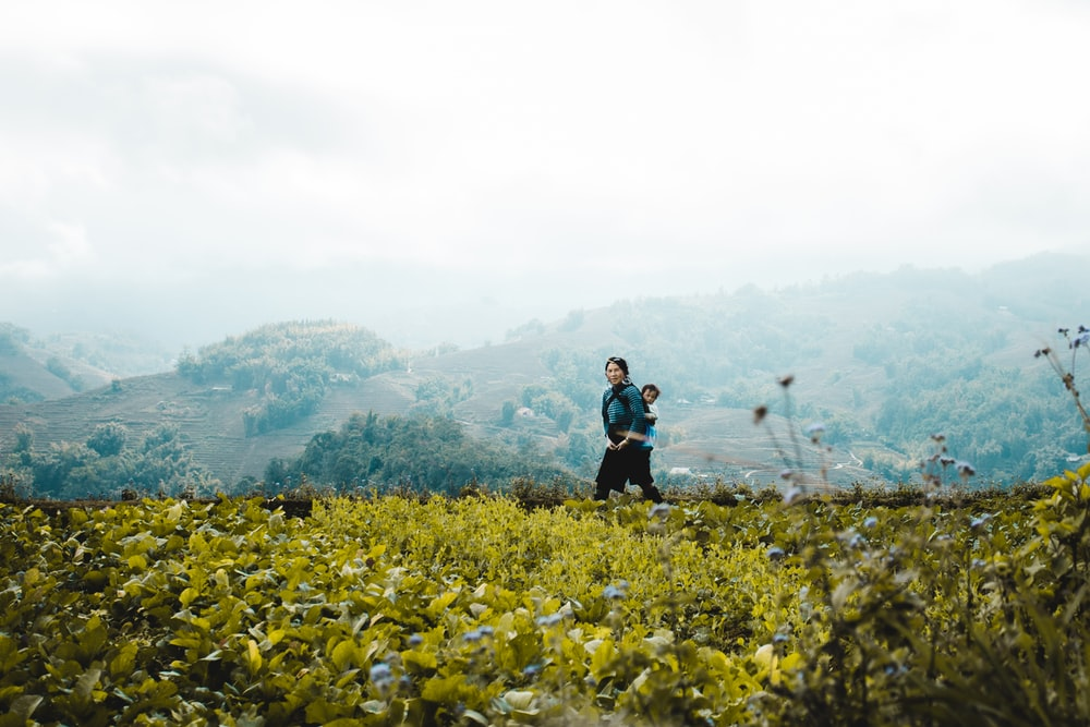 woman in black jacket standing on yellow flower field during daytime