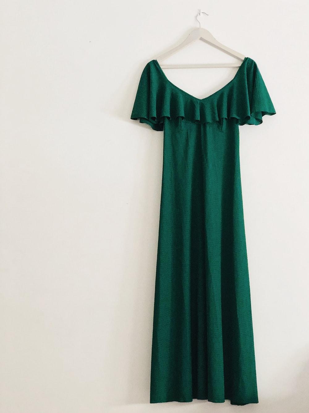 green sleeveless dress hanged on white wall