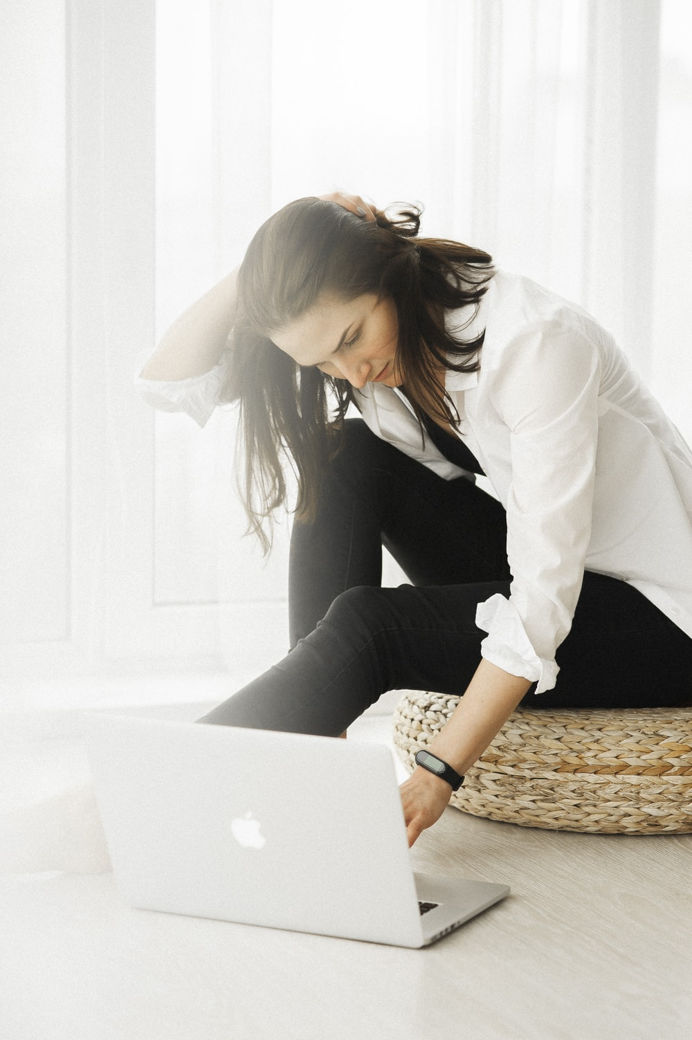 woman in white long sleeve shirt and black pants sitting on brown wicker chair