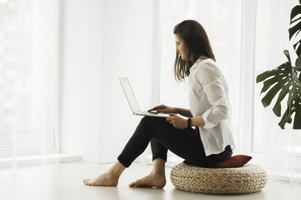 woman in white long sleeve shirt and black pants sitting on brown woven chair