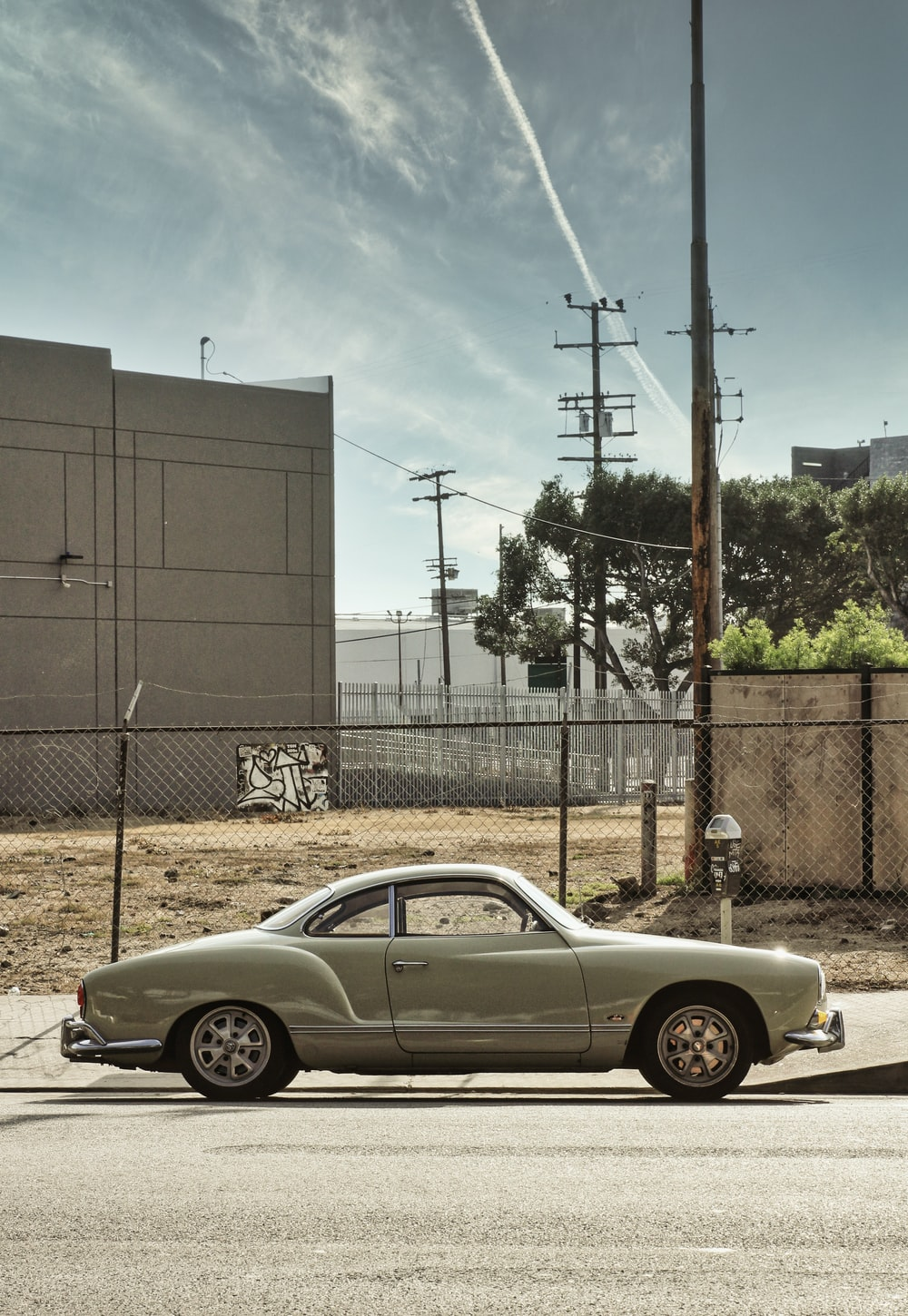 silver coupe parked beside gray metal fence