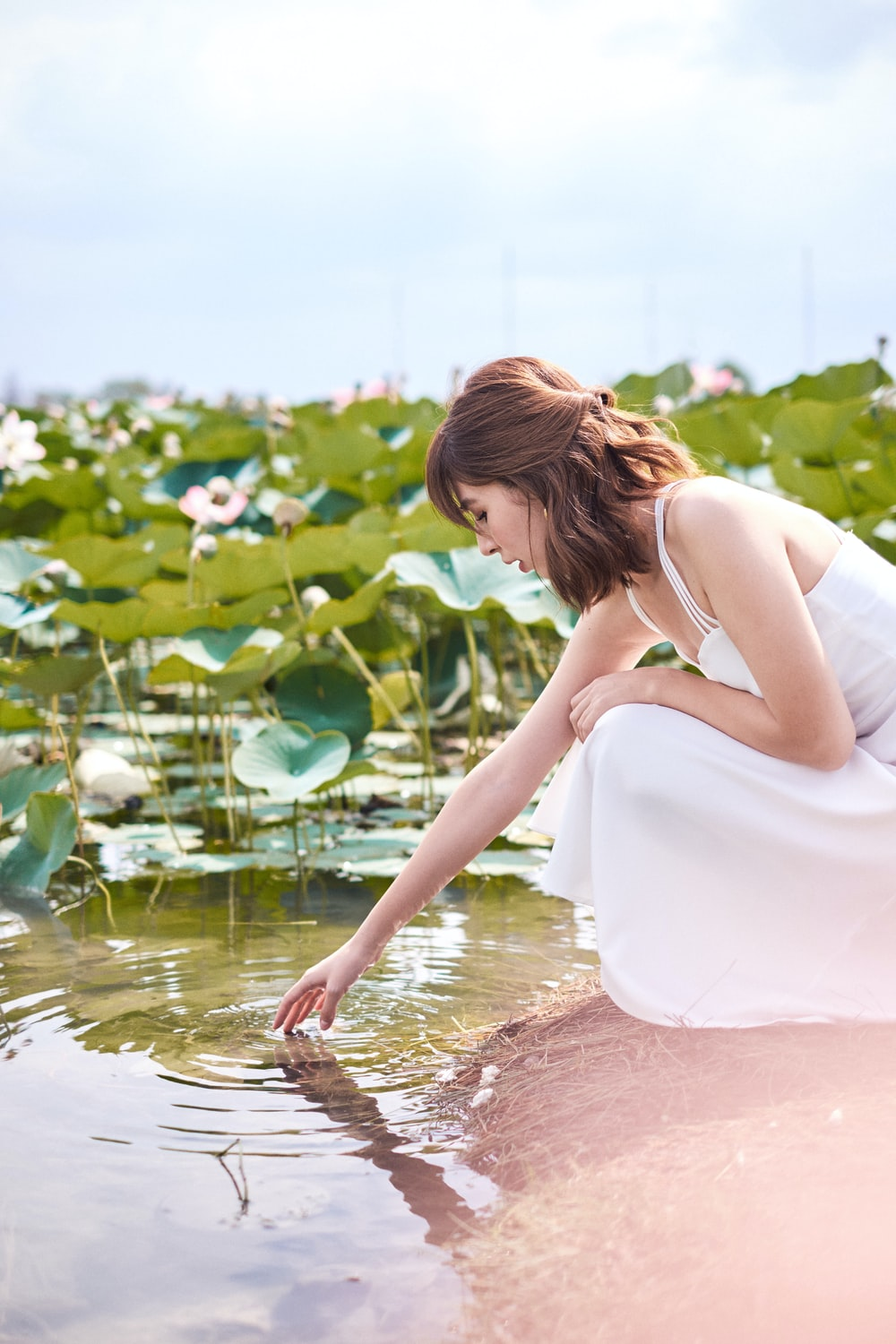 woman in white tank dress on water