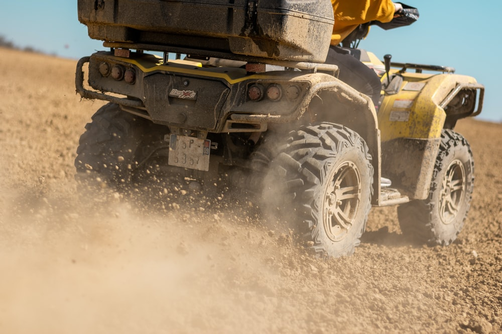 yellow and black front loader on beach during daytime