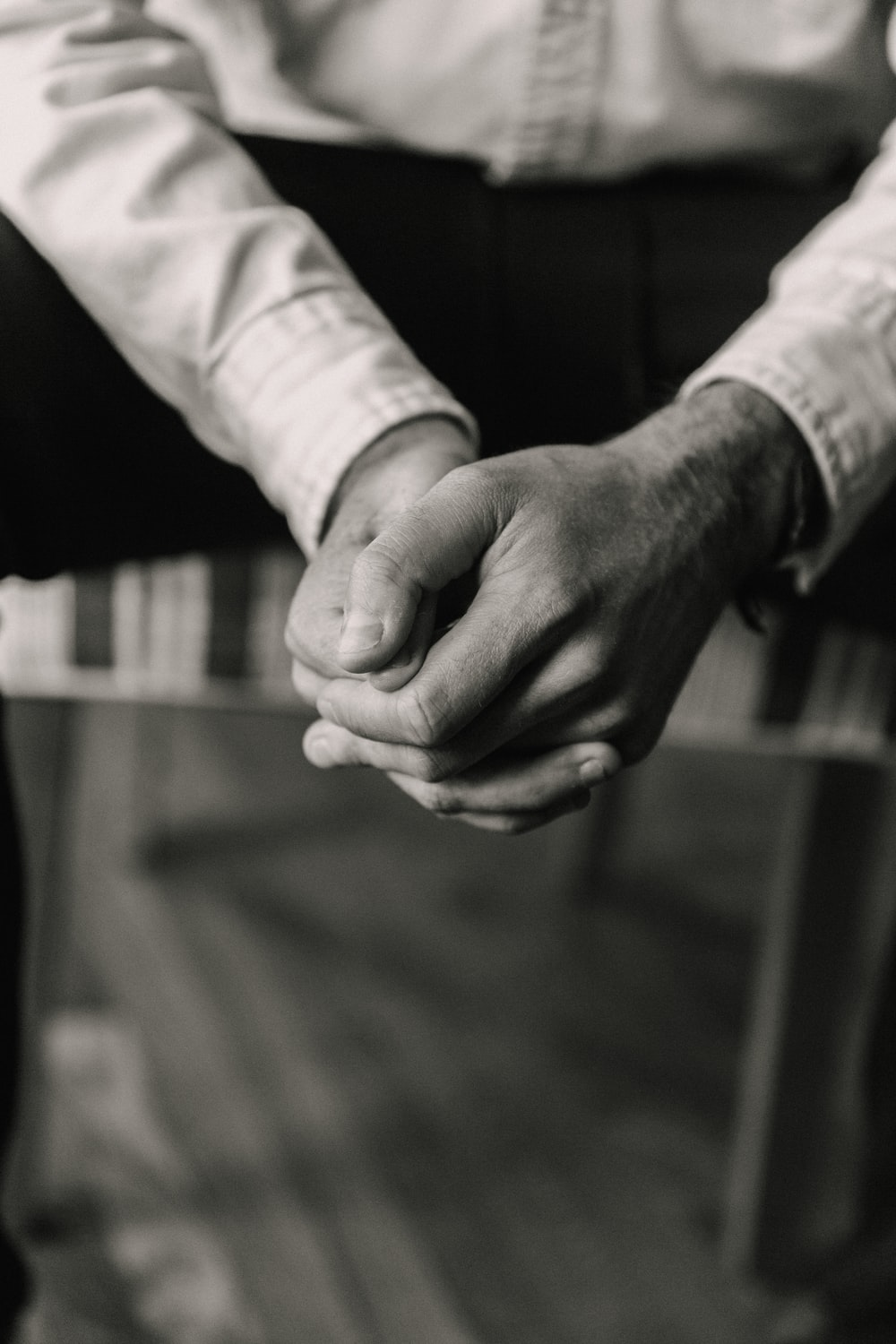grayscale photo of man and woman holding hands