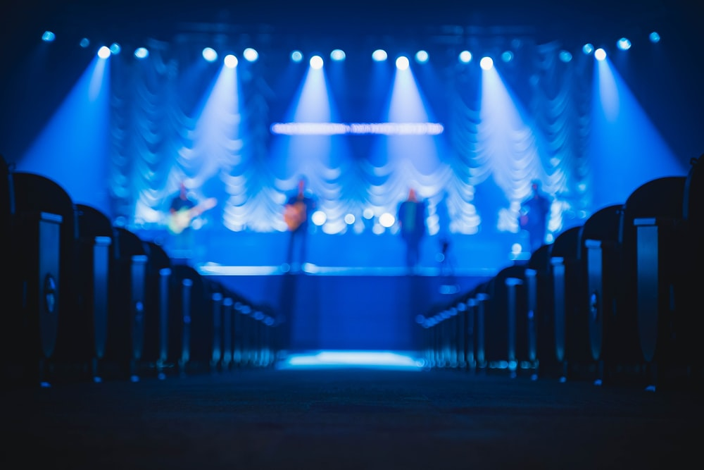 people standing on stage with blue lights
