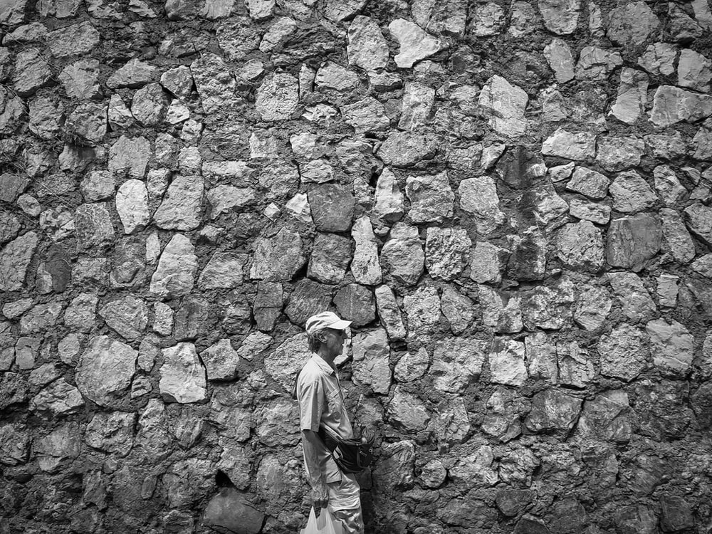 grayscale photo of man in long sleeve shirt and pants standing on brick wall