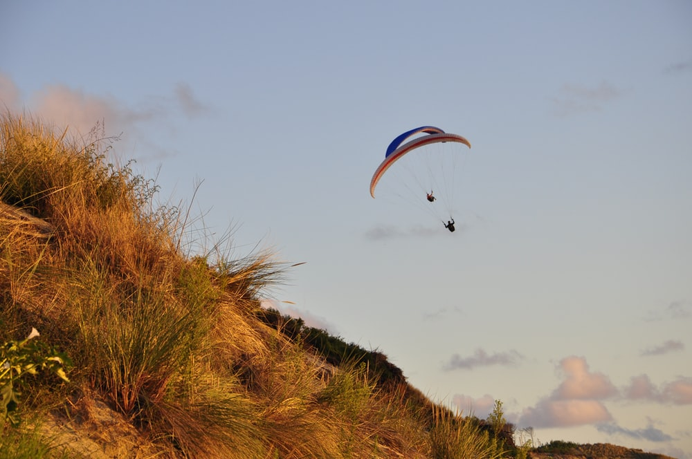 person in parachute over green grass field during daytime
