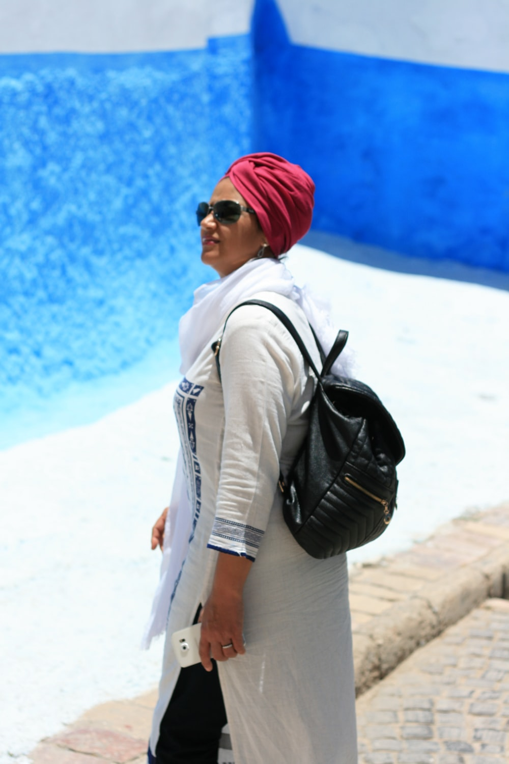 woman in white jacket and red knit cap standing on white sand during daytime