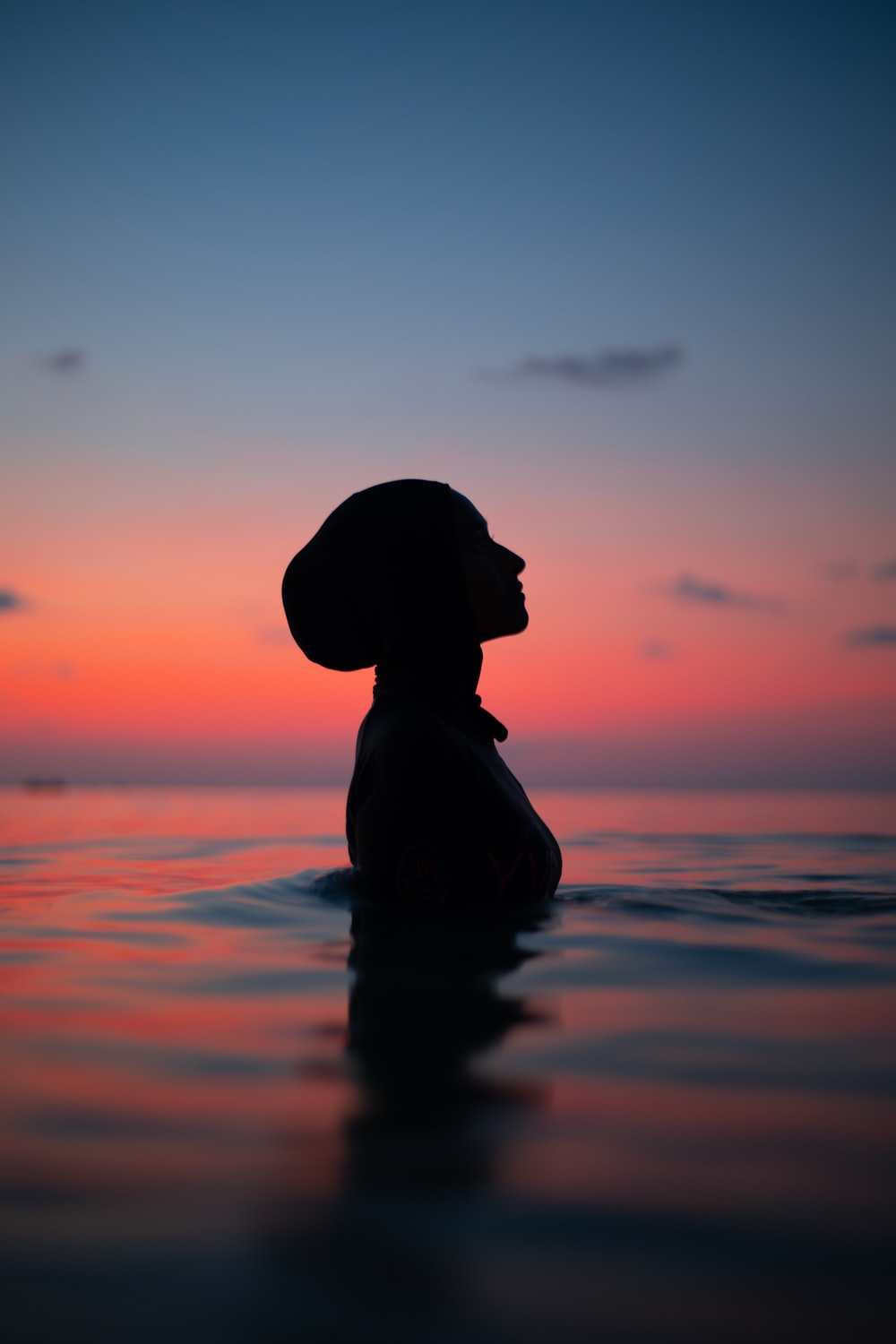 silhouette of woman wearing sun hat on water during sunset
