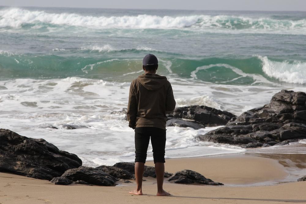man in brown jacket standing on seashore during daytime