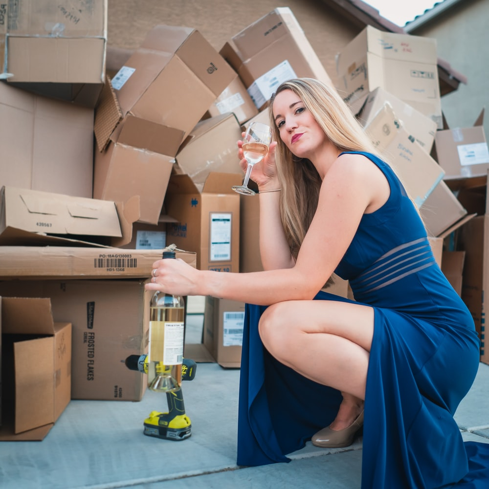 woman in blue sleeveless dress sitting on brown cardboard box