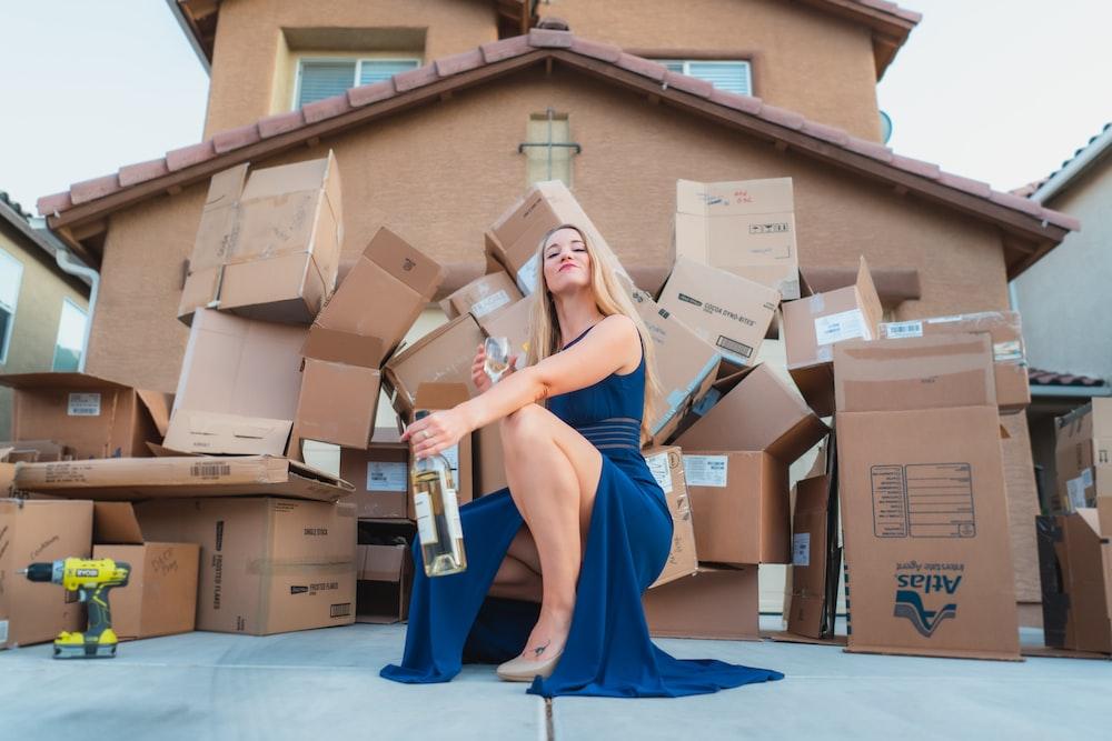 woman in blue dress holding brown cardboard box