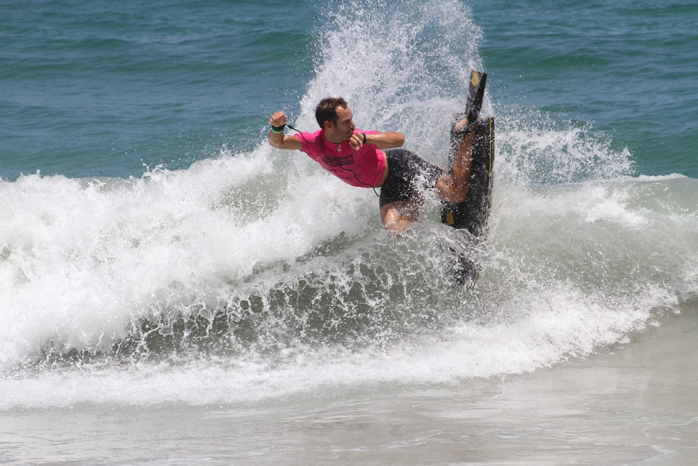 man in red shirt surfing on sea waves during daytime