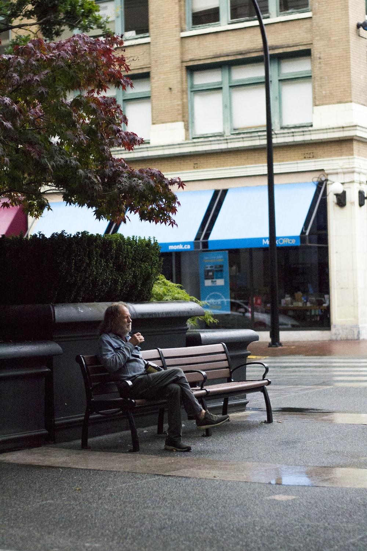 woman in black jacket sitting on black bench