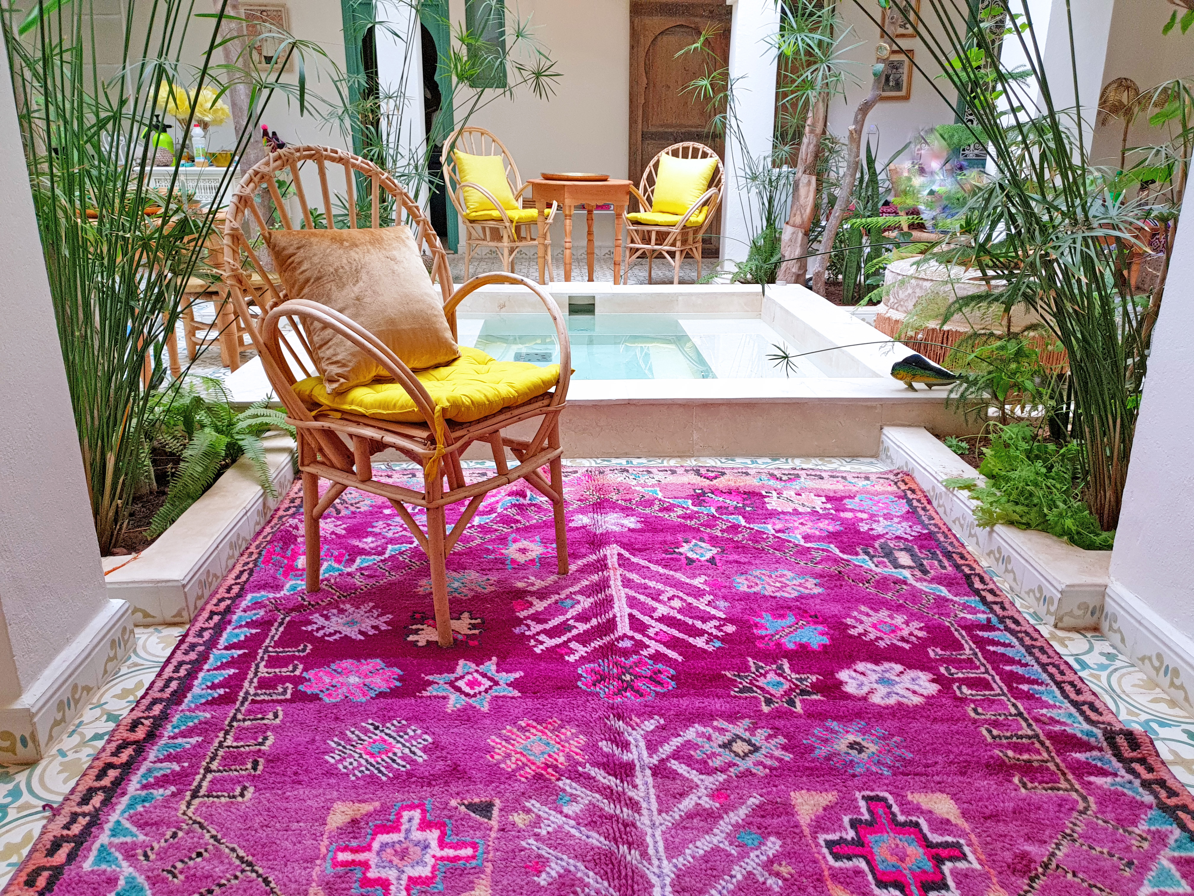 Boujad Rugs, hand-woven, one-of-a-kind rugs from the Middle Atlas region of Morocco. They typically feature asymmetrical geometric patterns and orange, pink, vibrant blue, and Fuschia color palettes. Boujads are primarily made from locally sourced wool, with occasional bits of cotton or acrylic. https://www.berberbazar.com/