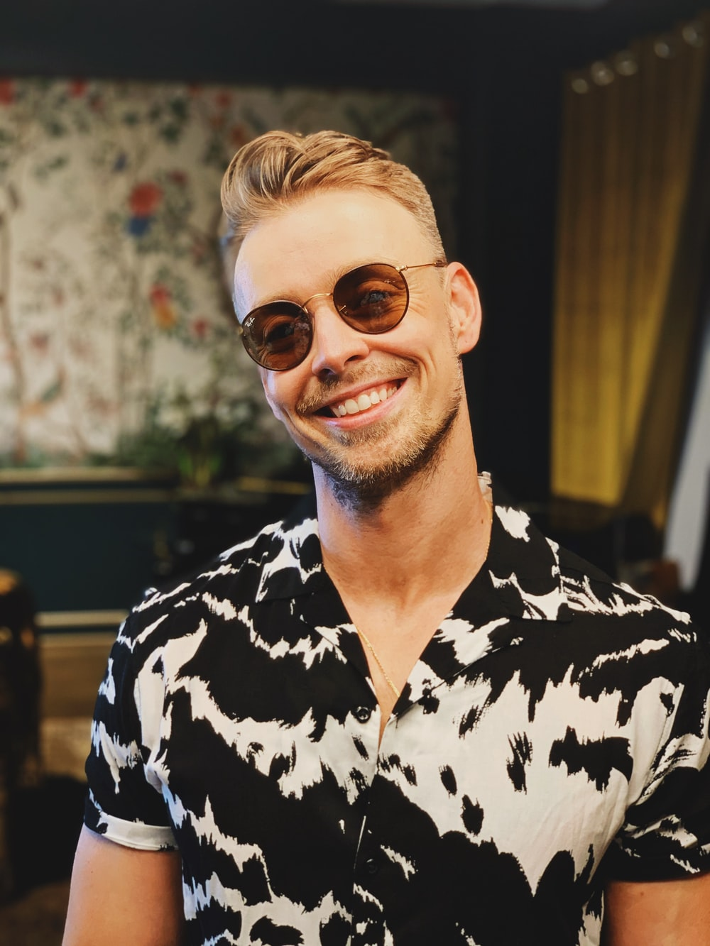 man in black and white floral button up shirt wearing brown sunglasses
