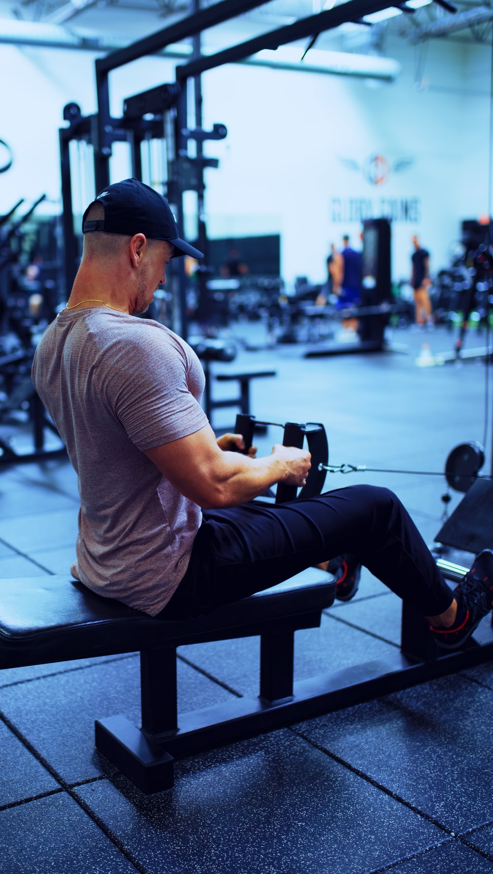man in gray t-shirt and blue denim jeans sitting on bench