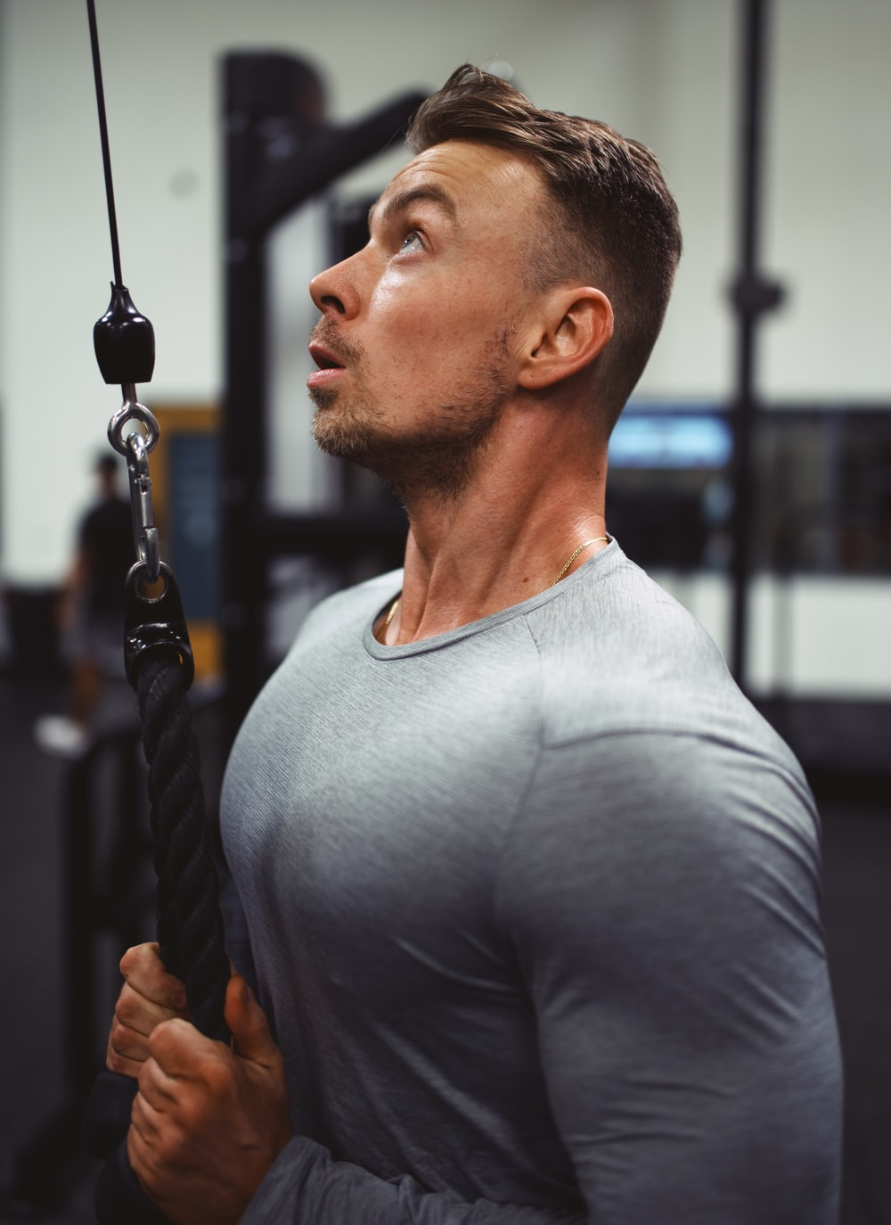 man in gray crew neck shirt holding black rope