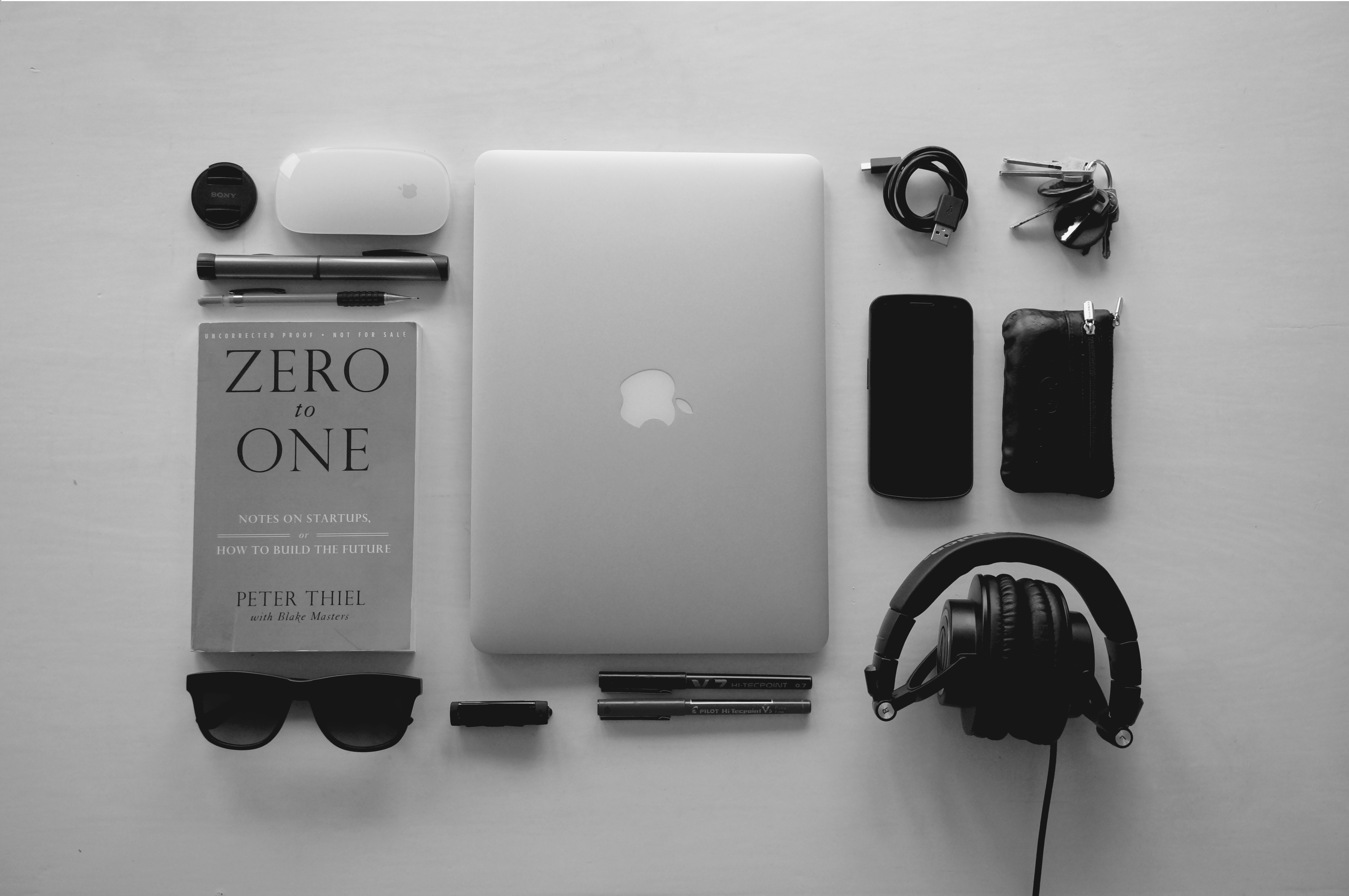 A neatly arranged collection of technology and gadgets including a laptop and Peter Thiel's book Zero to One