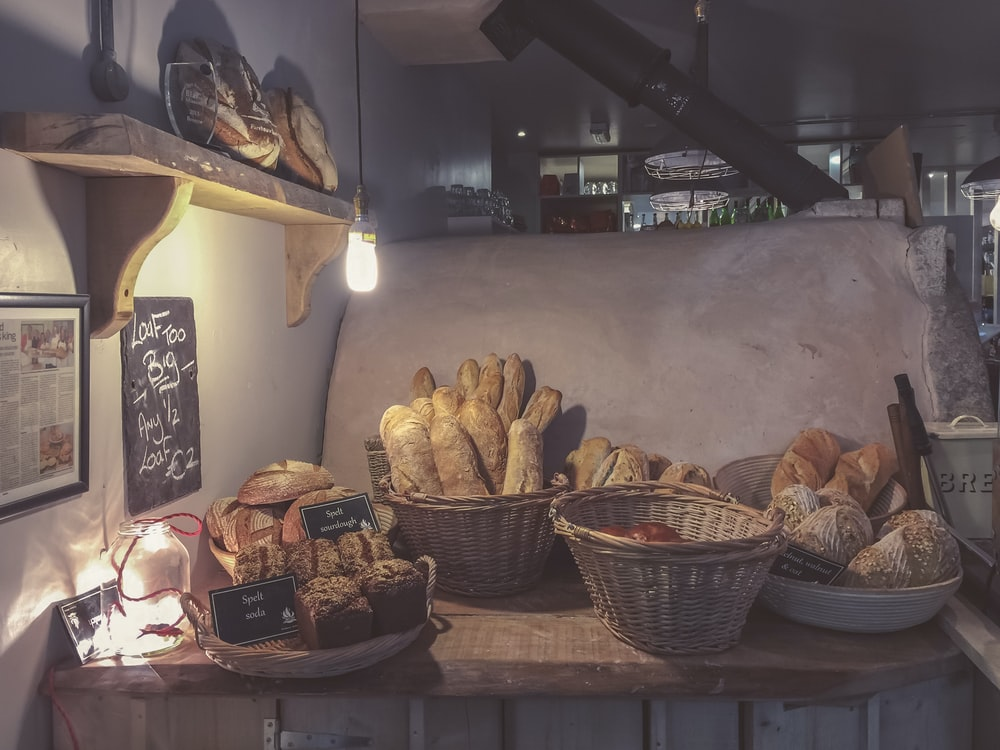 breads in brown wicker basket on top of brown wooden table