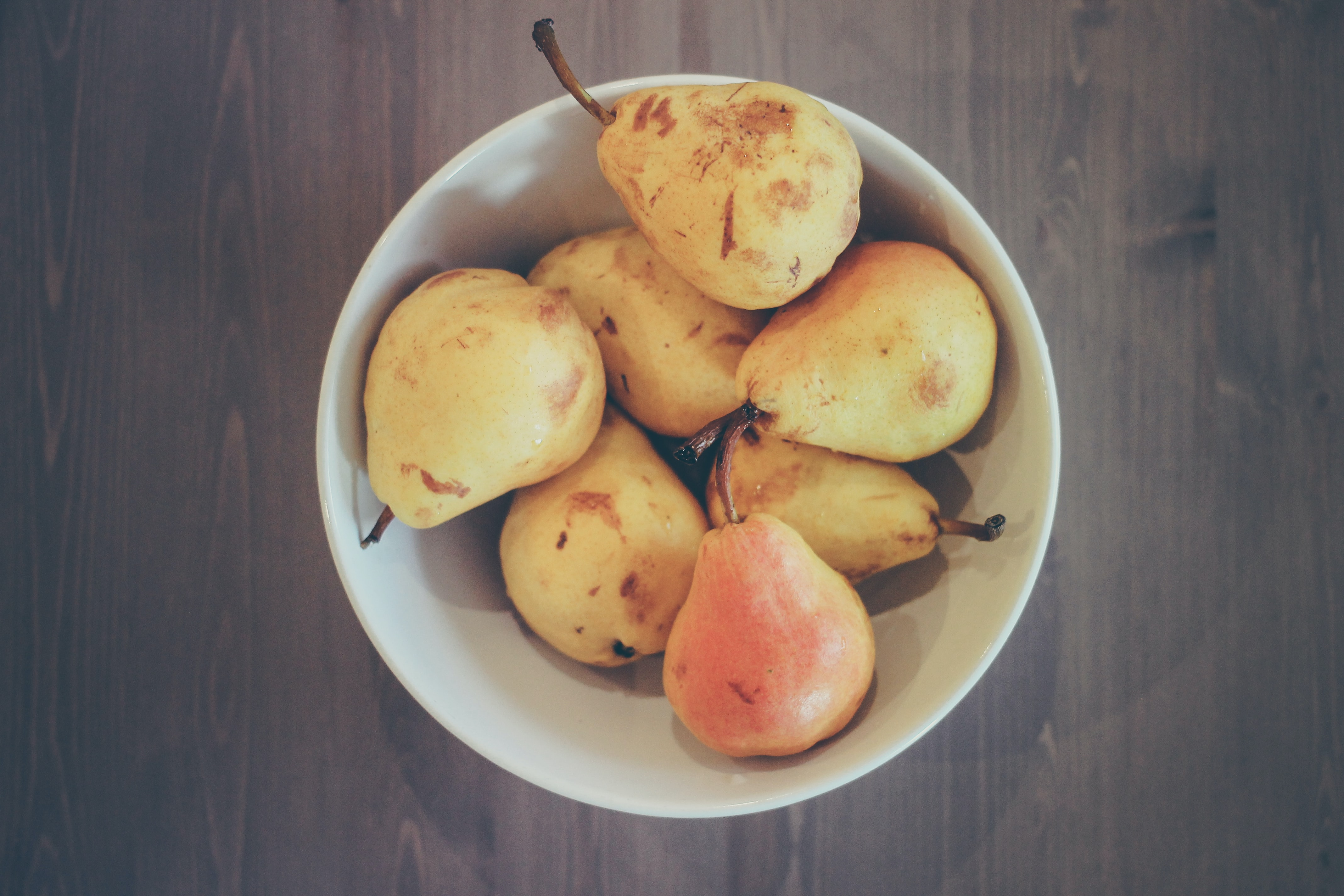 flat lay photography of bowl of ripe pear fruits