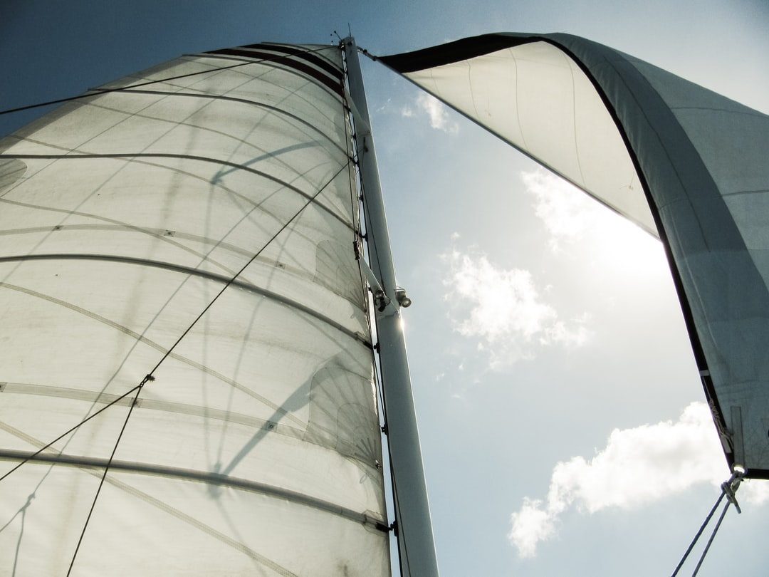 Looking up at white canvas sailboat sails in the wind