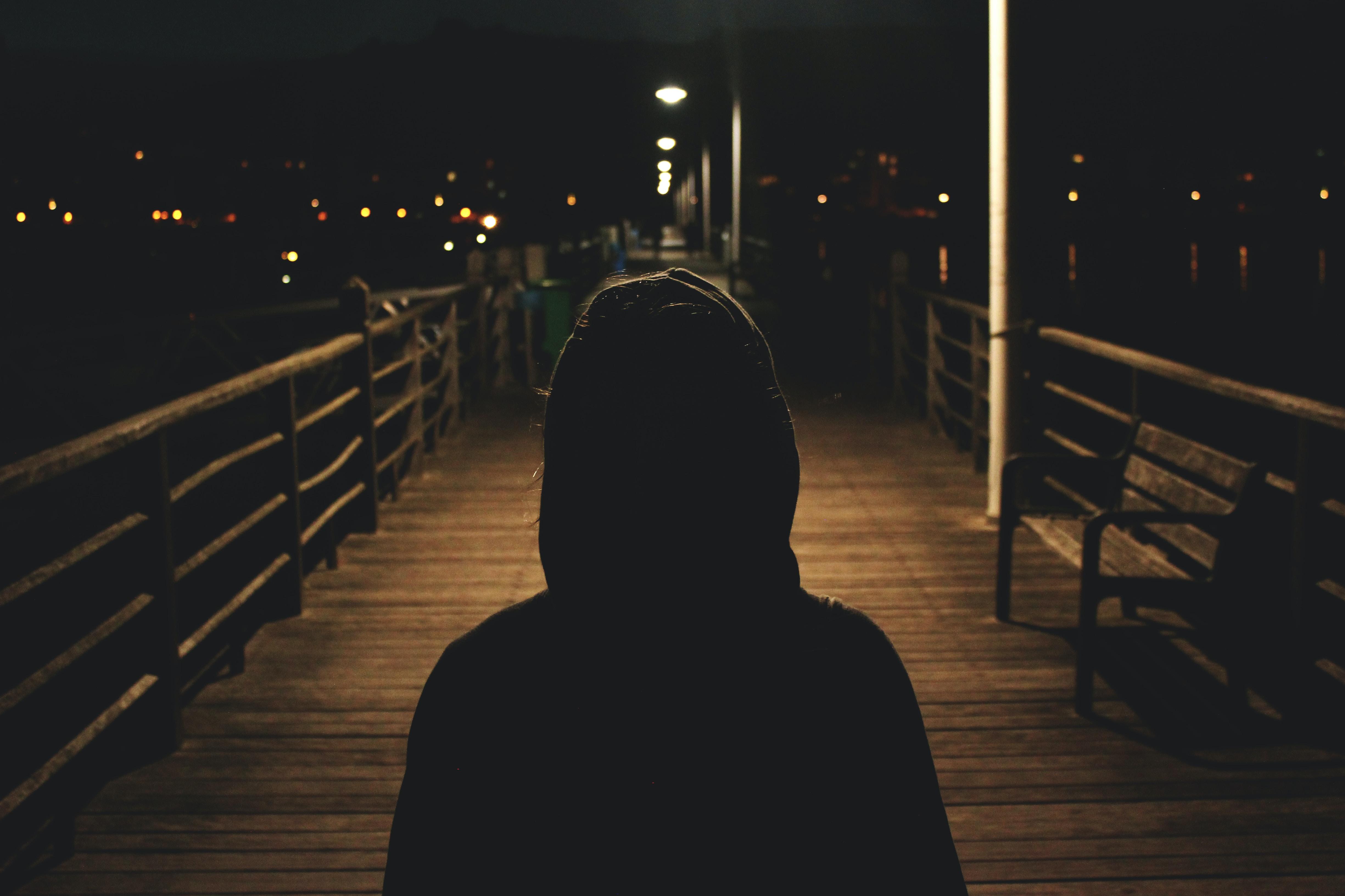 person wearing hooded jacket walking in bridge