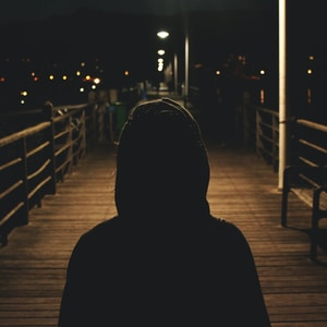 person wearing hooded jacket walking in bridge