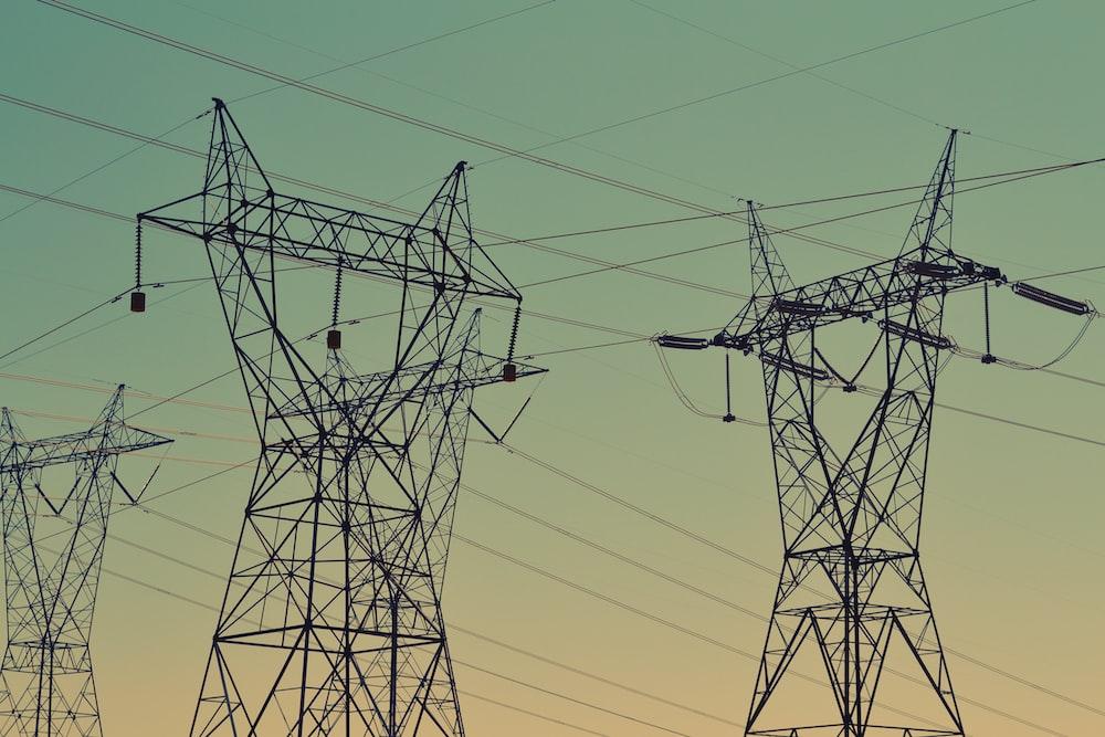 black transmission towers under green sky
