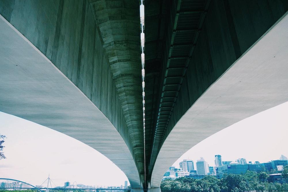 low angle photo of gray concrete bridge