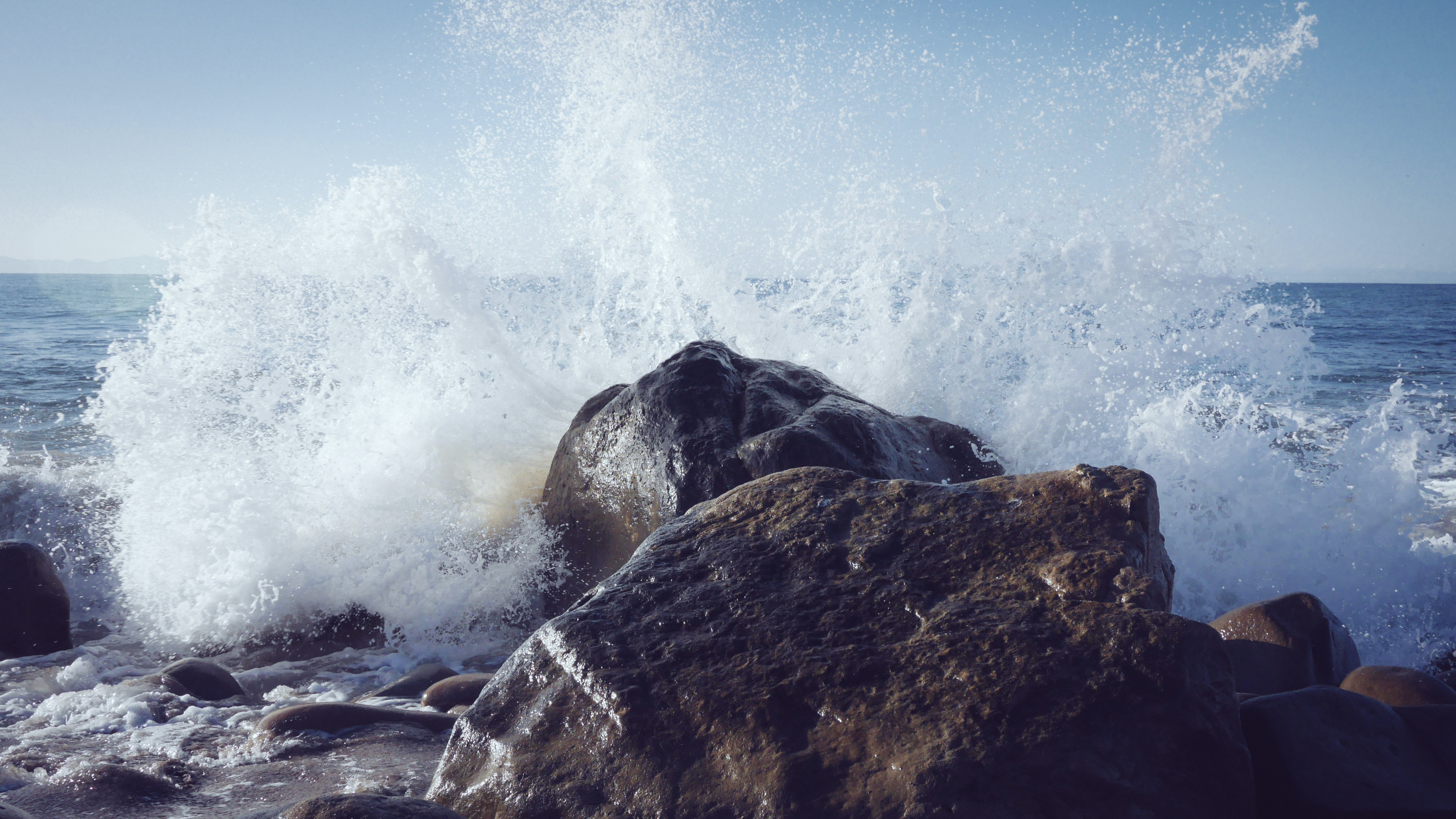 A wave splashing into a coastal rock, causing spray