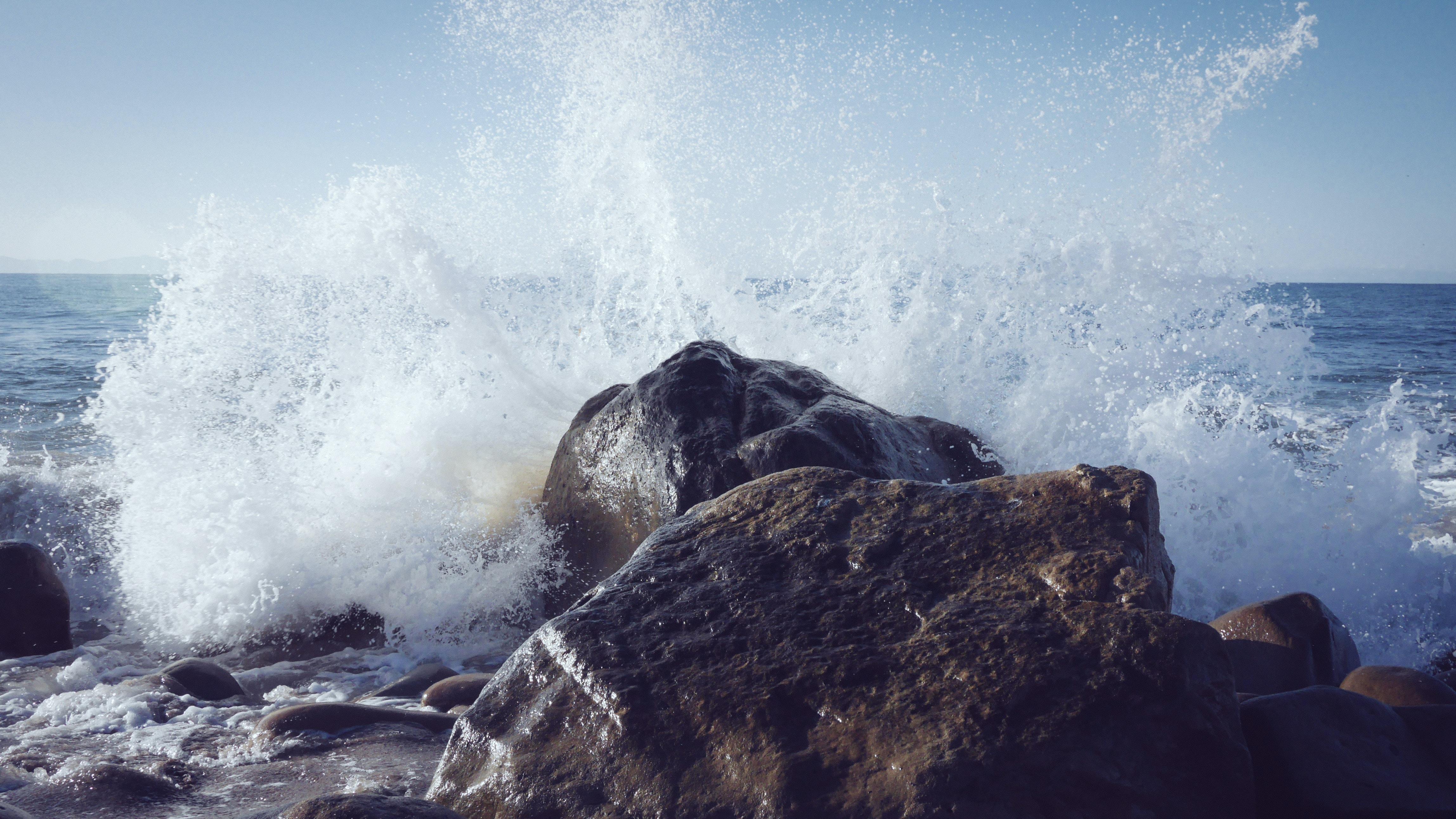A wave splashing into a coastal rock, causing spray