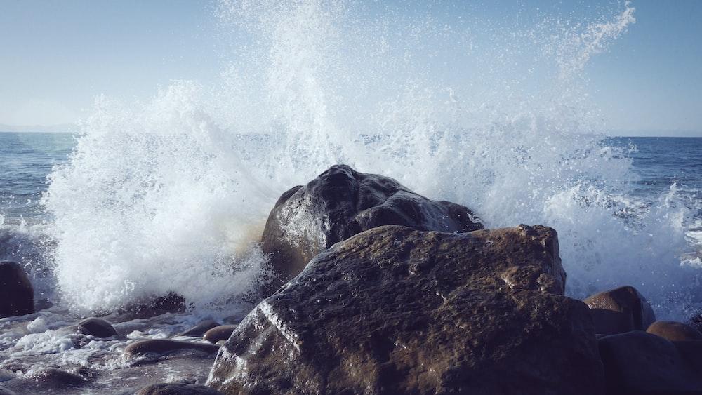 seashore splashed on rock during daytime